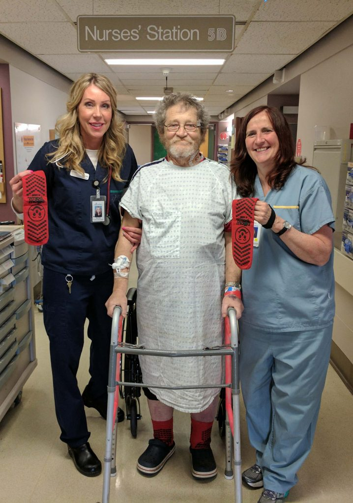 Rachel Garner, Clinical Nurse Leader, and Lucy Wilkinson, Physiotherapist, assist a patient wearing red socks to help raise awareness about falls prevention at St. Paul's Hospital.